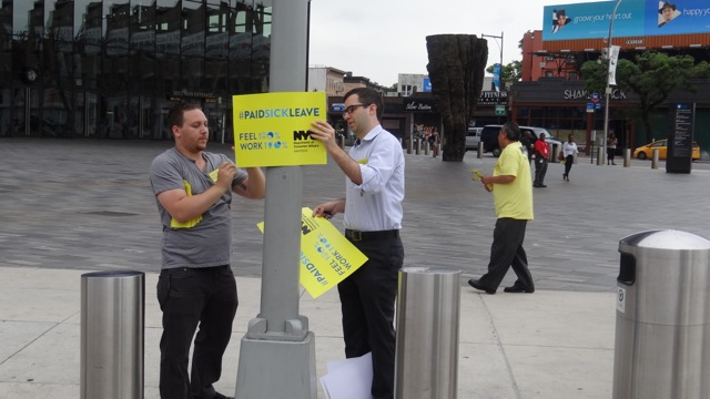 Campaigners outside the subway station at Barclays Center, putting up posters to inform residents about the Paid Sick Leave Law