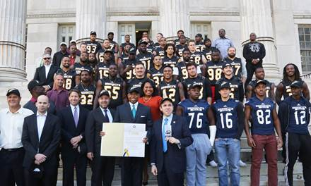 Brooklyn Borough President Eric L. Adams, sporting a new Brooklyn Bolts cap, presents a citation to the Bolts of the Fall Experimental Football League (FXFL), the borough¹s first professional football team since 1949, at a rally on the steps of Brooklyn Borough Hall; in addition to the members of the Bolts in the background, he is joined by (from left to right) Bolts Head Coach John Bock, FXFL Commissioner Brian Woods, New York Mets Chief Operating Officer Jeff Wilpon, Brooklyn Chamber of Commerce President and CEO Carlo A. Scissura, Special Counsel to the Brooklyn Borough President Ama Dwimoh, Council Member Mark Treyger and members of the Brooklyn Technical High School Engineers. Photo: Kathryn Kirk/BP¹s Office