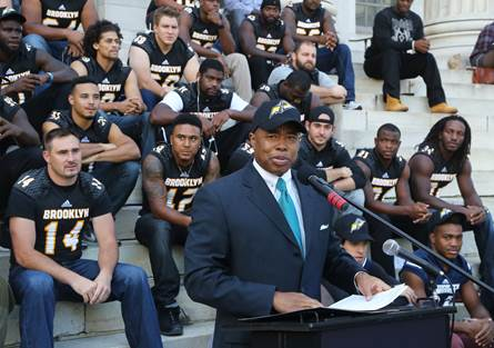 Brooklyn Borough President Eric L. Adams, sporting his new Brooklyn Bolts cap, welcomes the Bolts of the Fall Experimental Football League (FXFL), the boroughÂs first professional football team since 1949, at a rally on the steps of Brooklyn Borough Hall; in the background are members of the Bolts. Photo: Kathryn Kirk/BP¹s Office
