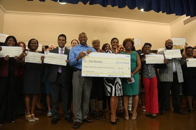 """Brooklyn Borough President Eric L. Adams joins Deputy Brooklyn Borough President Diana Reyna, teachers, and school administrators from across Brooklyn in the auditorium of PS 193 Gil Hodges as he announced over $13 million invested in 70 schools throughout the borough; he held an oversized check made out to """"One Brooklyn"""" for STEM education."""
