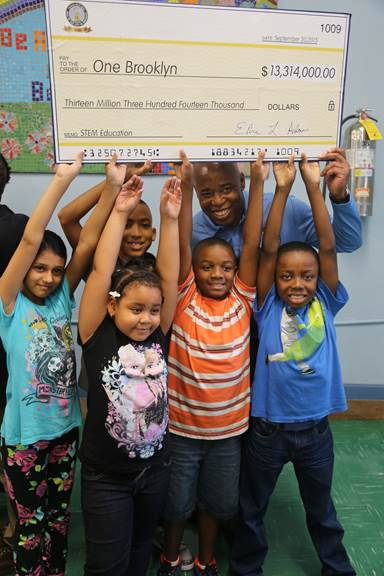 """Brooklyn Borough President Eric L. Adams joins students from PS 193 Gil Hodges in raising up an oversized check in the amount of $13,314,000 made out to """"One Brooklyn"""" for STEM education; he visited their school to announce the investment from his Fiscal Year 2016 funds in 70 schools throughout the borough. Photo Credit: Stefan Ringel/Brooklyn BP's Office"""