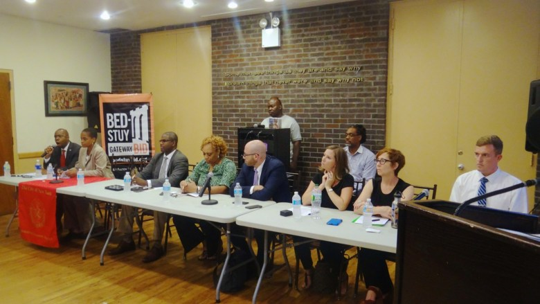 Panelist at the town hall meeting: (l to r) Henry Butler, CB3 District Manager; Tremaine Wright, CB3 Chair; Michael Lamber, Bed-Stuy Gateway BID; Marian Maura, DHS; Matthew Gordon, DHS, Claire Sheedy, Vice President of housing operations and programs, Breaking Ground; Amy Pospifil, Deputy VP, Breaking Ground; Doug Becht, VP, Breaking Ground