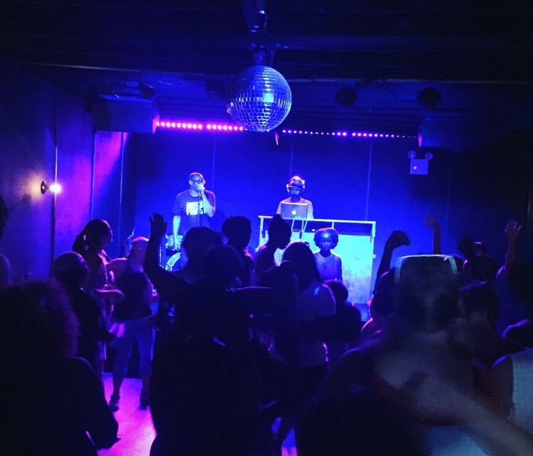 People dance to music in a room lit with blue and purple. A dj plays music in the back.