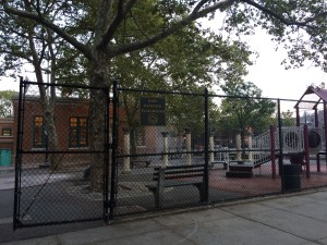 """A playground on the other side of a fence. A tree grows in the middle of several benches and columns. A sign labels the park """"John Hancock Playground."""""""
