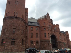 An angled view of the front of the 23rd Regiment Armory on Beford and Atlantic. The brick and stone building has a turret foregrounded on the left.