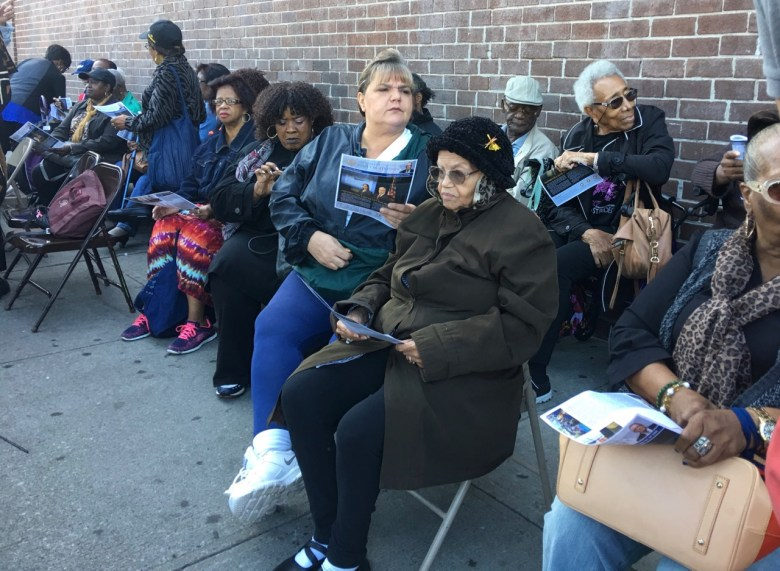 Senior members of the Fort Greene Senior Citizens Council sit outside of the senior center during the announcement