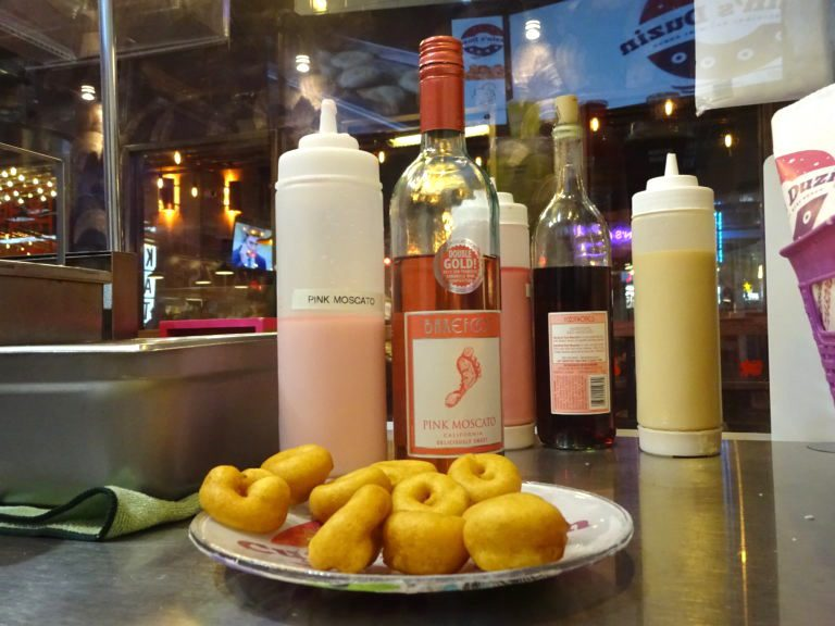 Cuzin's Duzin's pink Moscato glaze adds a fruity flavor to the fluffy donuts.