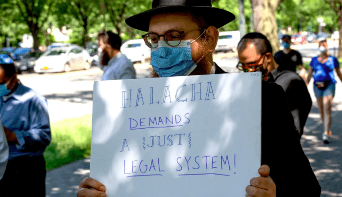 A Hasidic man carries a sign saying Jewish religious law demands a just legal system. Photo: Mo Gelber.