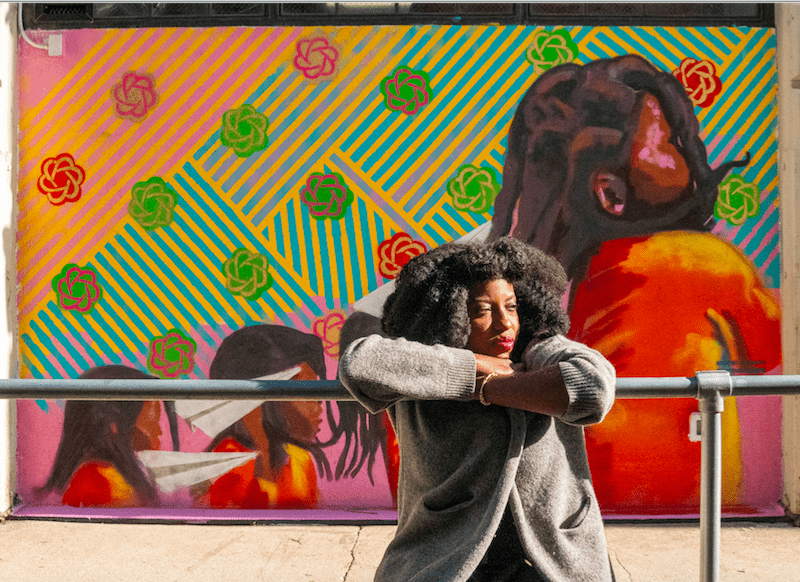 """Artist Sophia Dawson with her mural, """"Paper Planes"""" at Industry City. Photo: Provided by Industry City."""