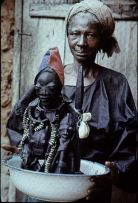 A traditional worshiper with a statue of esu