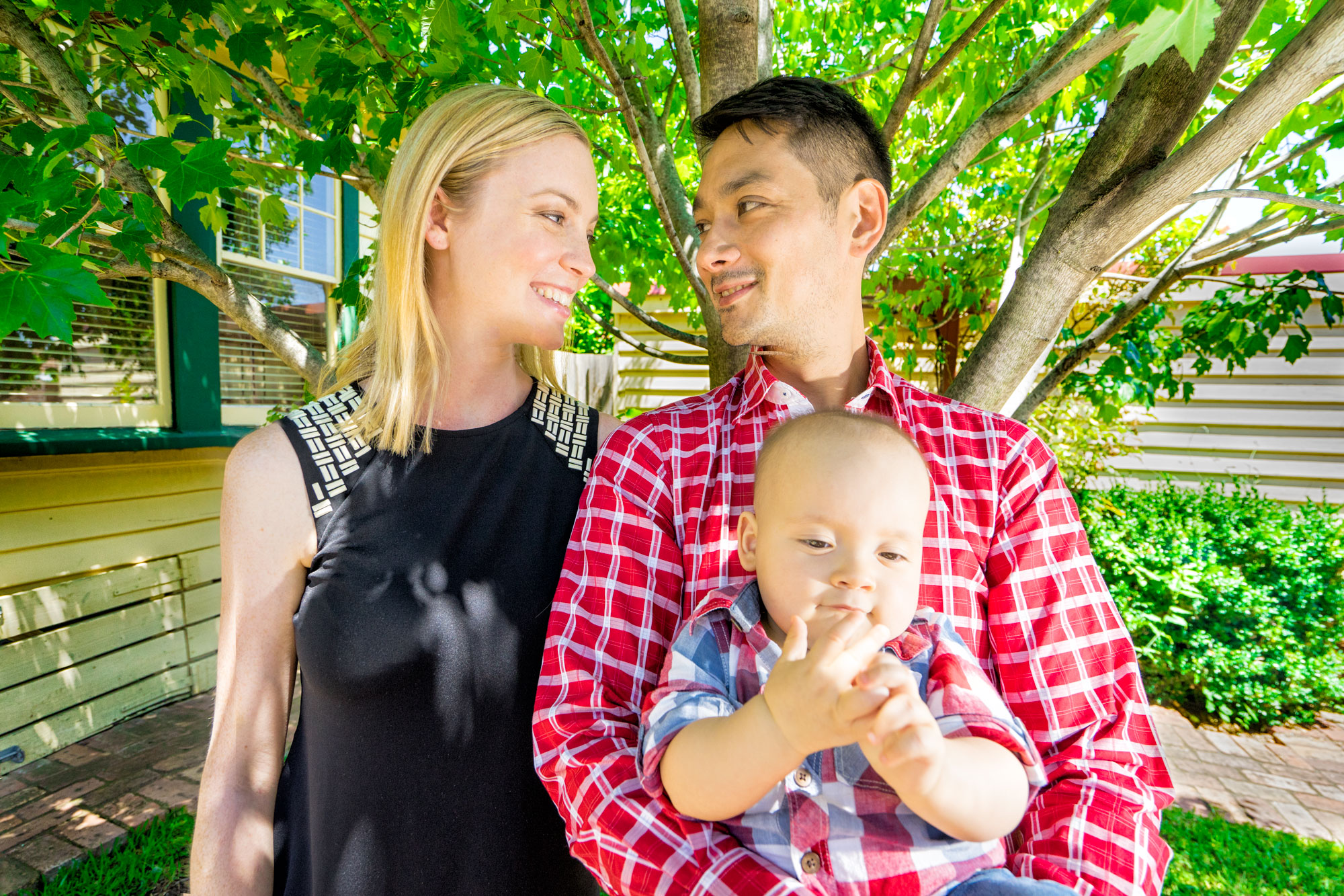 Young family looking at each other relaxed at their backyard for photo