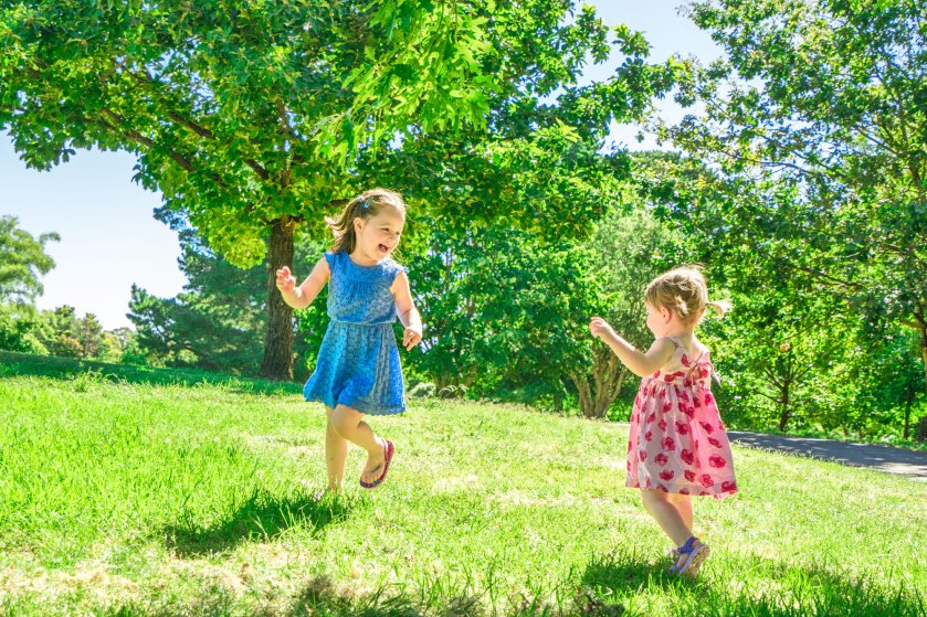 Sister chasing each other during family portrait session by Black Avenue Productions