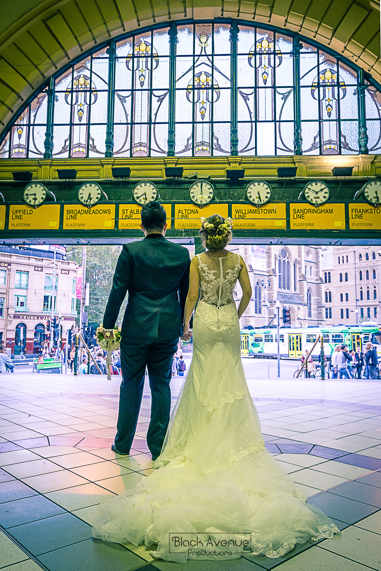 Melbourne couple taking photo at Flinder Street train station wedding photo by Black Avenue Productions