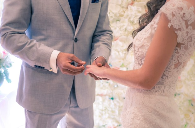 candid moment of bride and groom exchange wedding ring during ceremony with flower wall background