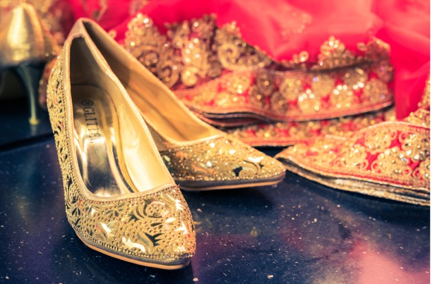 golden wedding shoes and red veil close up image for wedding photography