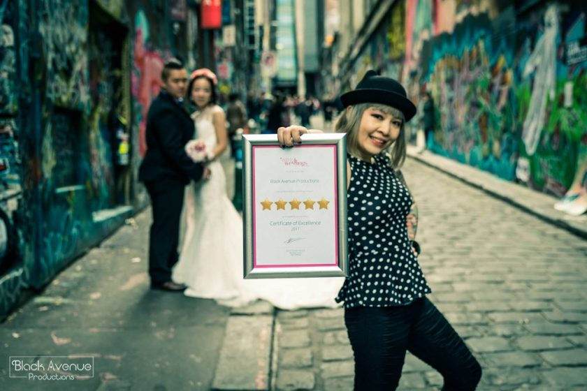 Proud female photographer holding a 5 star award winning frame by Easy Weddings posing in front of just married couple in CBD graffiti lane