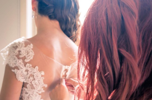 red head bridesmaid helping bride to button up her lace back wedding gown at their Southbank home for wedding photo