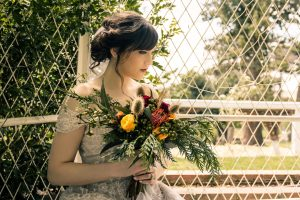 beautiful bride in her latte colour full bridal gown from Leah S Design holding a bunch of trendy forest wheat grass flower bouquet sitting in Overnewton Castle captured by Black Avenue Productions