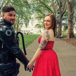 star wars engagement photo showing cosplay tie pilot holding hand to vintage pinup red polka dot dress wife at Fitzroy garden