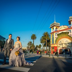 Hong Kong couple wearing wedding bridal outfit walking in front of St Kilda Luna Park for their Engagement photography Melbourne
