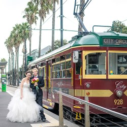 bride and groom standing in front of vintage city circle tram in Dockland Melbourne
