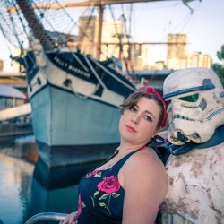 pinup girl and sand trooper posing for their pre wedding photo by Black Avenue Productions with a boat background