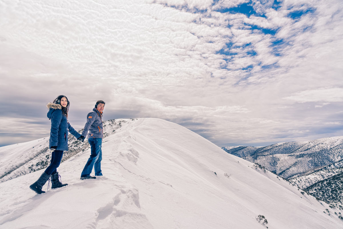 Melbourne couple hold hands walk on Falls Creek snow mountain for their winter engagement photo shoot by Black Avenue Productions