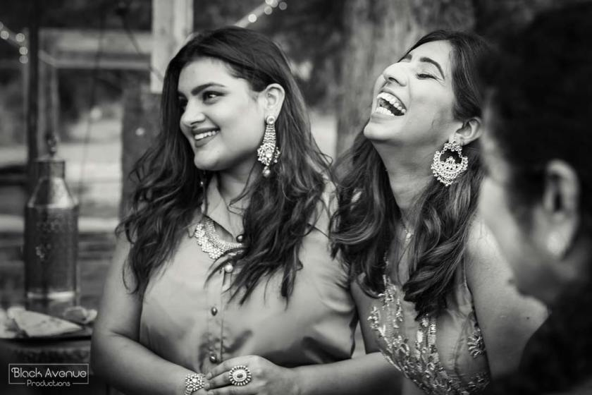 real candid moment of two girls laughing happily at their Baxter Barn melbourne wedding reception in black and white image