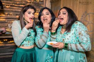 three cute bridesmaids cheekily eat wedding cakes in Baxter Barn in Melbourne