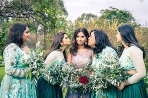 bridal party photo inspiration of bridesmaids kissing the bride in the middle holding on woodland greenery wedding setting