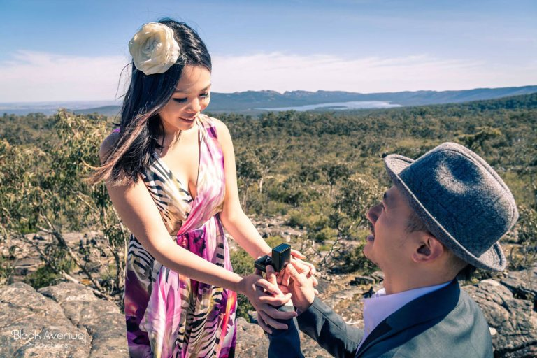 happy girlfriend accepting her engagement ring during a surprise marriage proposal moment captured by Black Avenue Productions in a stunning hilltop view sunrise