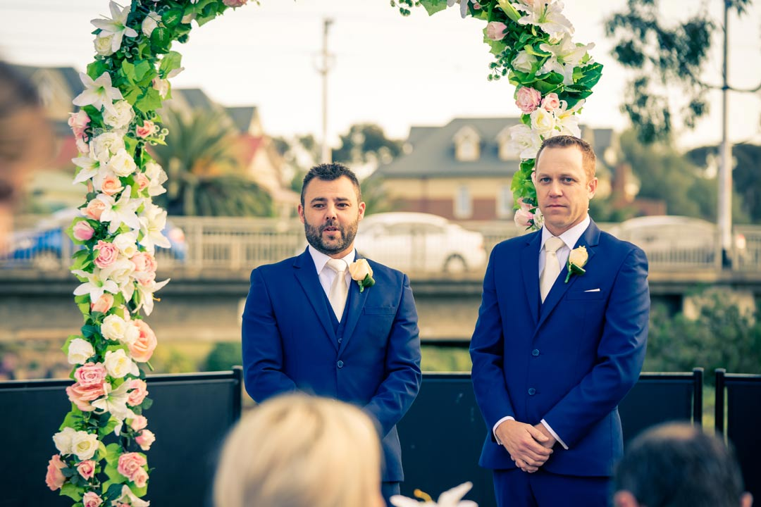 nervous groom and groomsman waiting for his bride to walk down the aisle