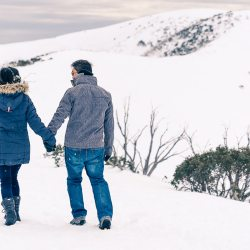 winter engagement photography showing young couple walking in snow mountain hand in hand in ski gear
