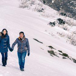 engaged couple having a walk on snow mountain for their pre wedding photo