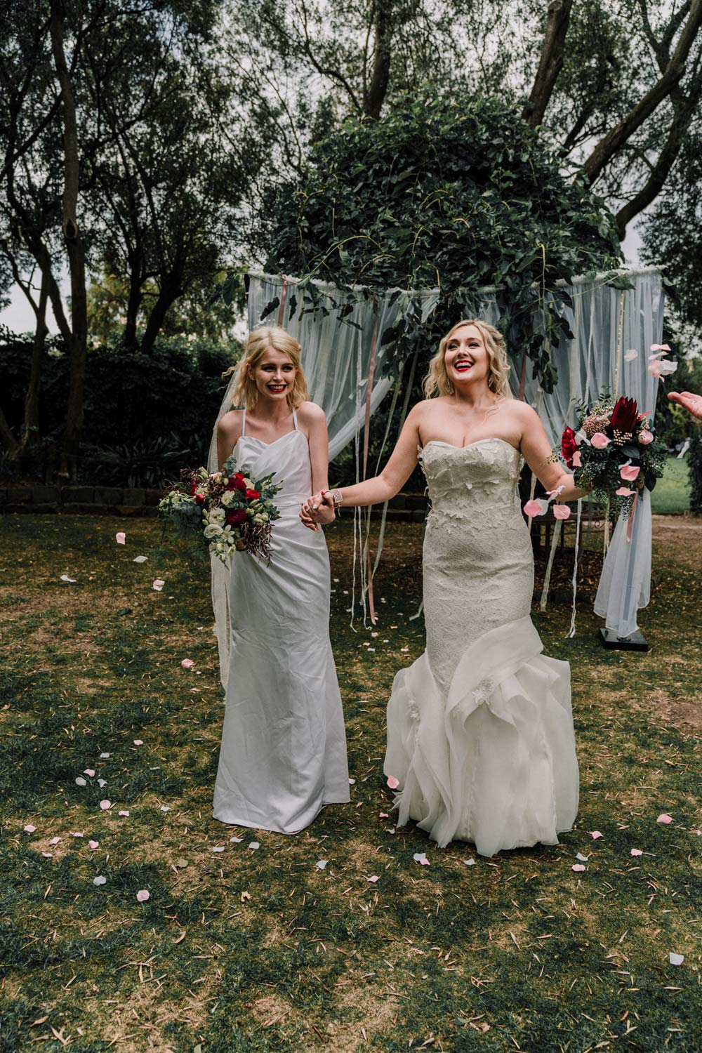 real lesbian wedding in Overnewton Castle showing lesbian bride happily walk down the aisle