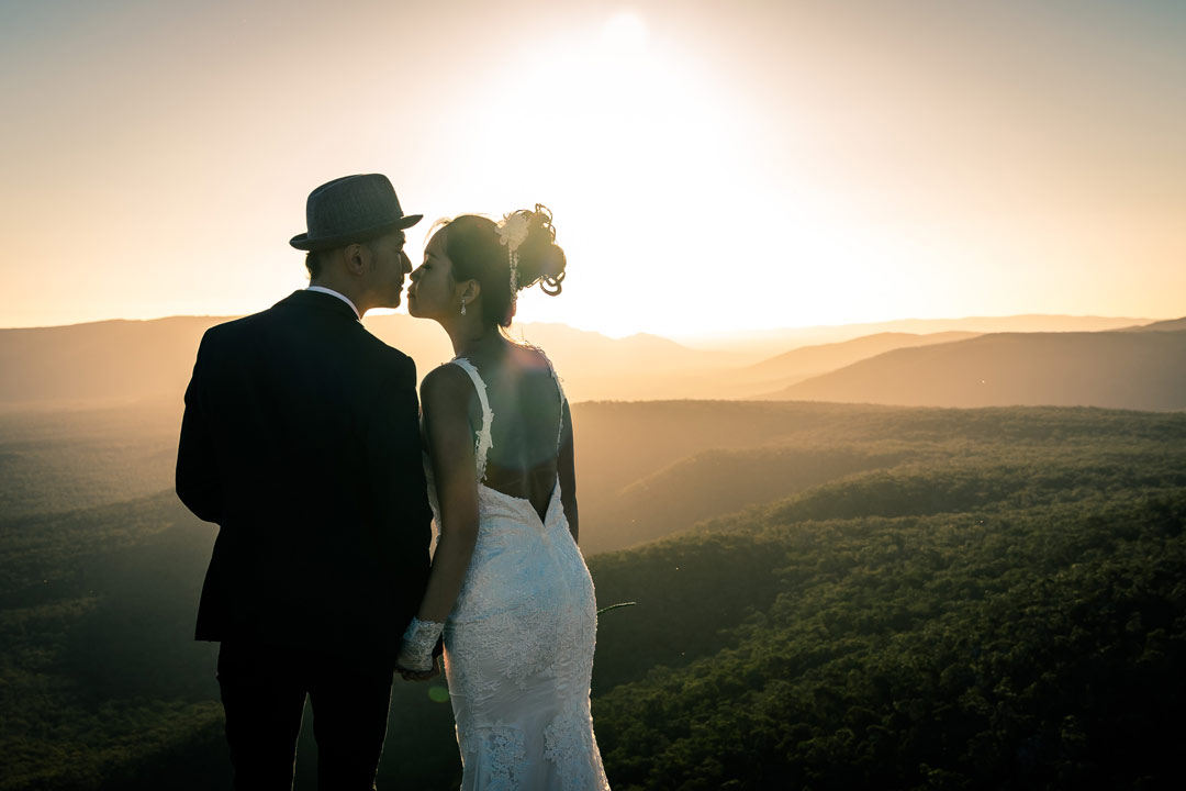 bride groom kissing in front of stunning sunset view on The Grampians hilltop