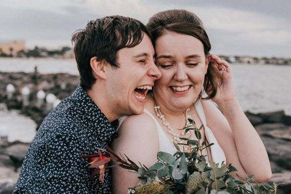 Laughing couple by the St Kilda beach on their wedding day capture by wedding photography company Black Avenue Productions