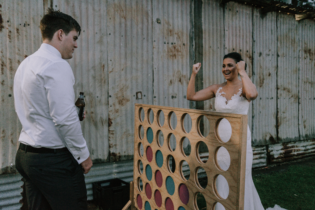 Mornington Peninsula married couple playing with board game during their barn wedding reception