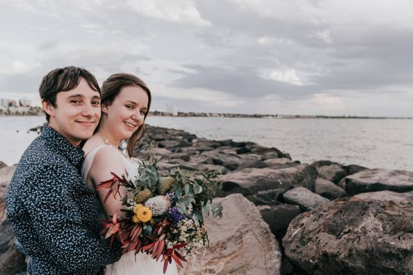 happy young couple holding boho bouquet posing for their St Kilda Little Blue wedding photo by Black Avenue Productions