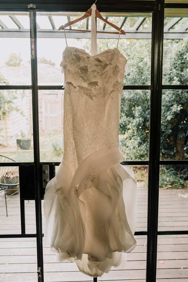 a stunning lace beading bridal gown hanging on a floor length window as part of bride prep photo by Melbourne wedding videographers Black Avenue Productions