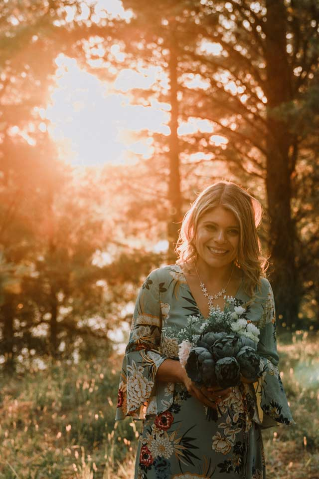 sweet girl holding a bunch of flower smiling in the Wilson Berwick Botanical Gardens in backlit photography style by Melbourne wedding photographer Black Avenue Productions