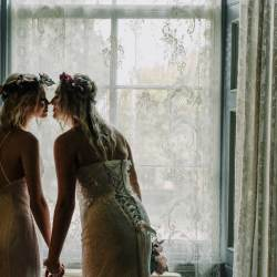 Melbourne same sex wedding photo showing two lesbian brides kissing by Overnewton Castle boho wedding reception captured by Black Avenue Productions
