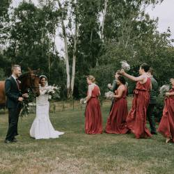 bridal party dancing at rustic farm wedding Melbourne with a horse in burgundy colour theme