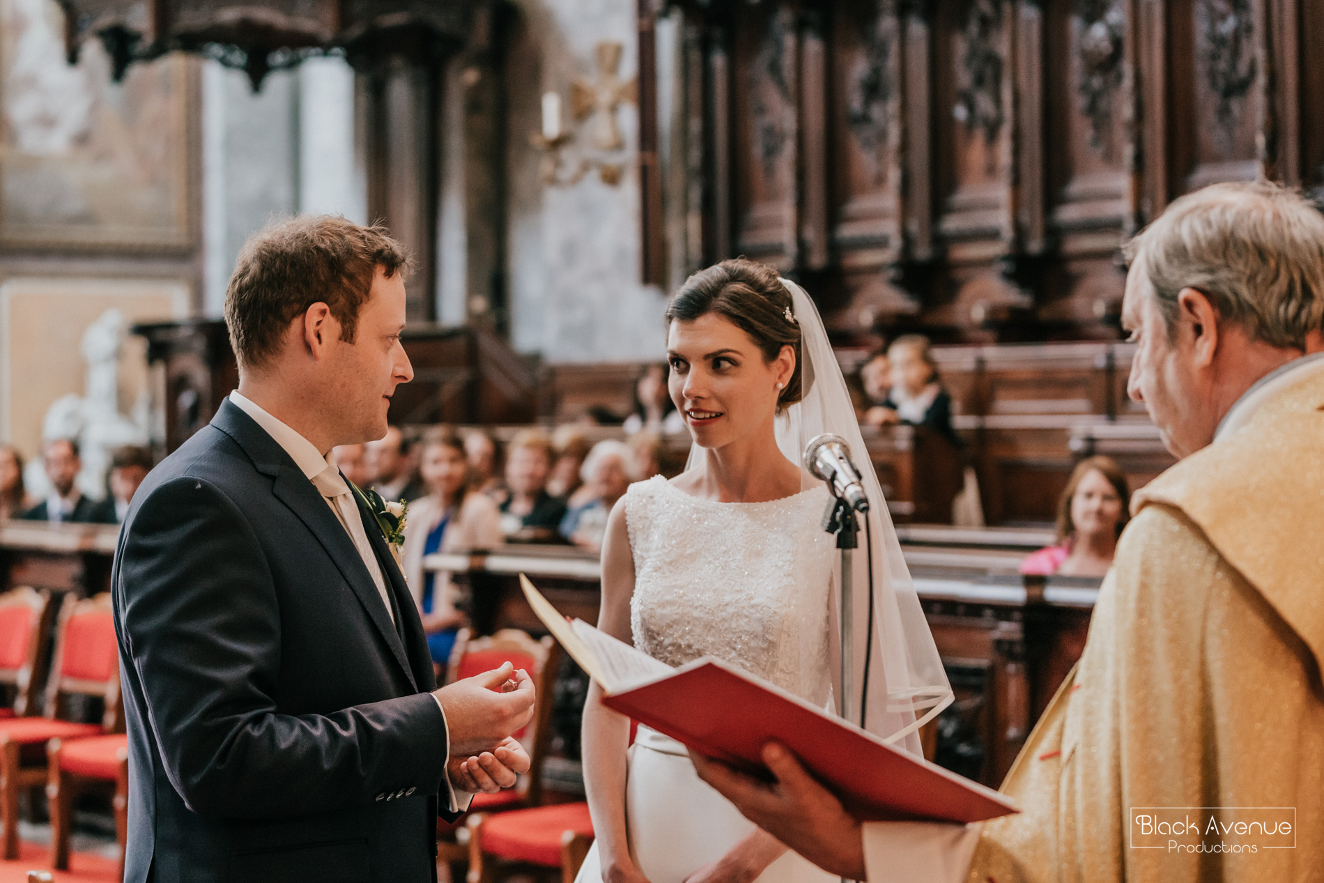 Candid moment of chapel wedding ceremony in the biggest church in Hungary by destination wedding photographers Black Avenue Productions