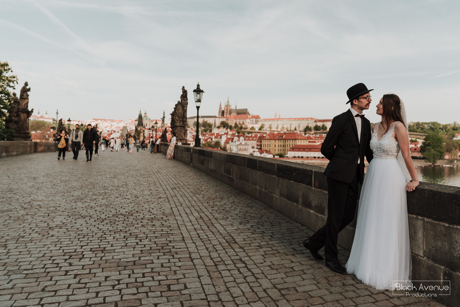 European bride and groom having a romantic moment in Prague Charles Bridge on their wedding day by destination wedding photographers from Australia