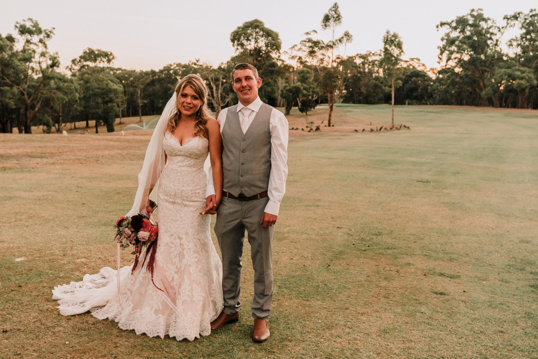Just married couple standing with kangaroo at Wilson Botanic Park Berwick wedding captured by award winning wedding photographer Derek Chan from Black Avenue Productions