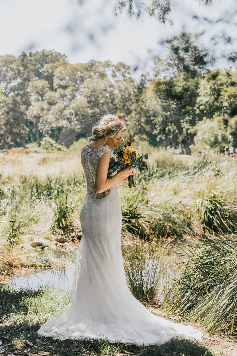 beautiful elegant bride smell kiss flowers bouquets in bush grass pond and shrub