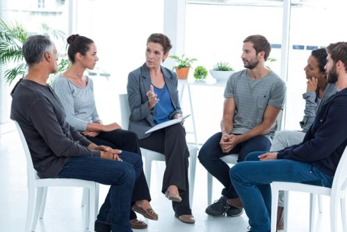 Adults sitting in a circle for group therapy