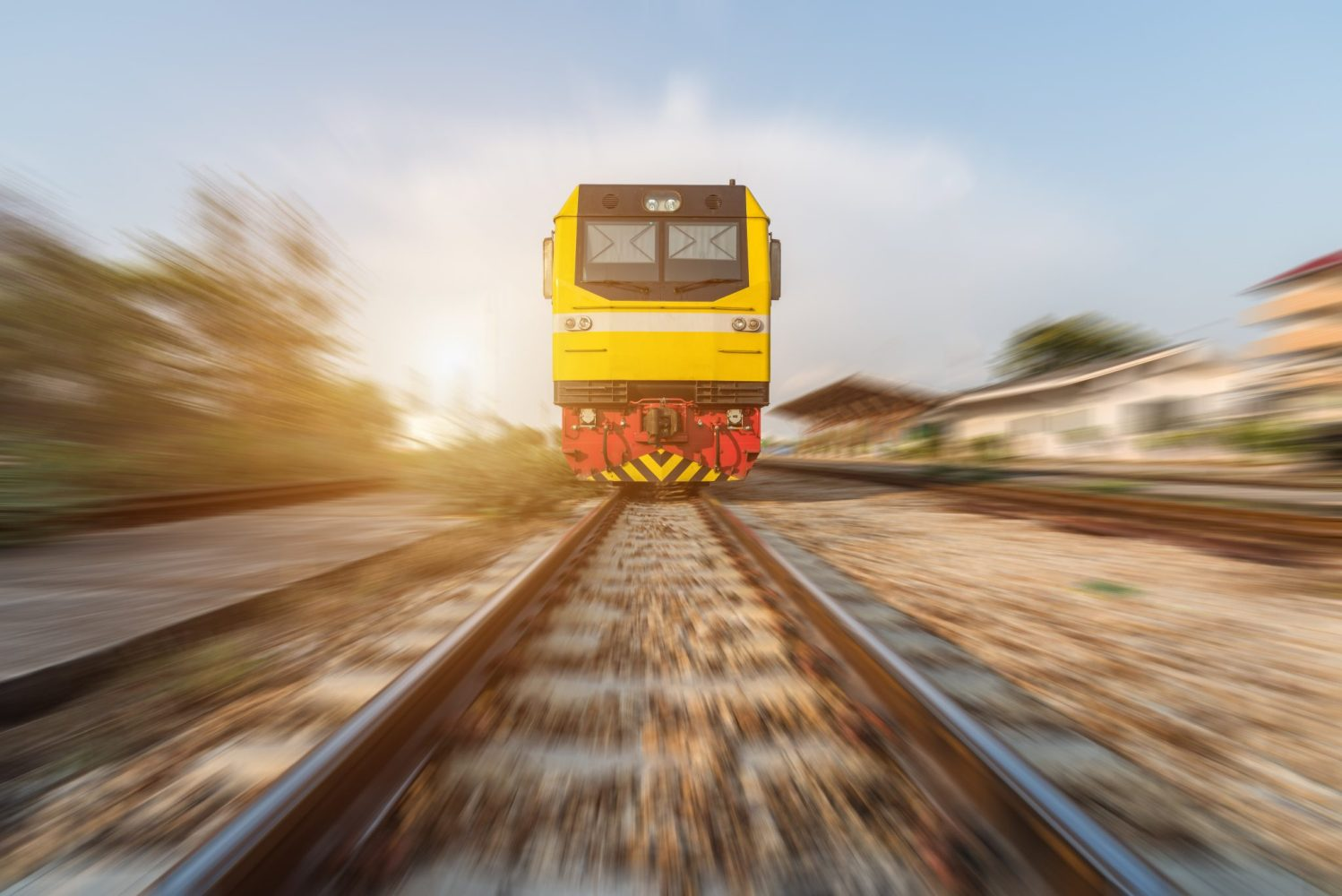 High speed diesel train on tracks with motion blur at sunset