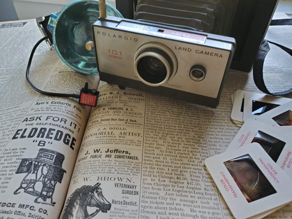 Old newspaper, antique Polaroid camera and slides